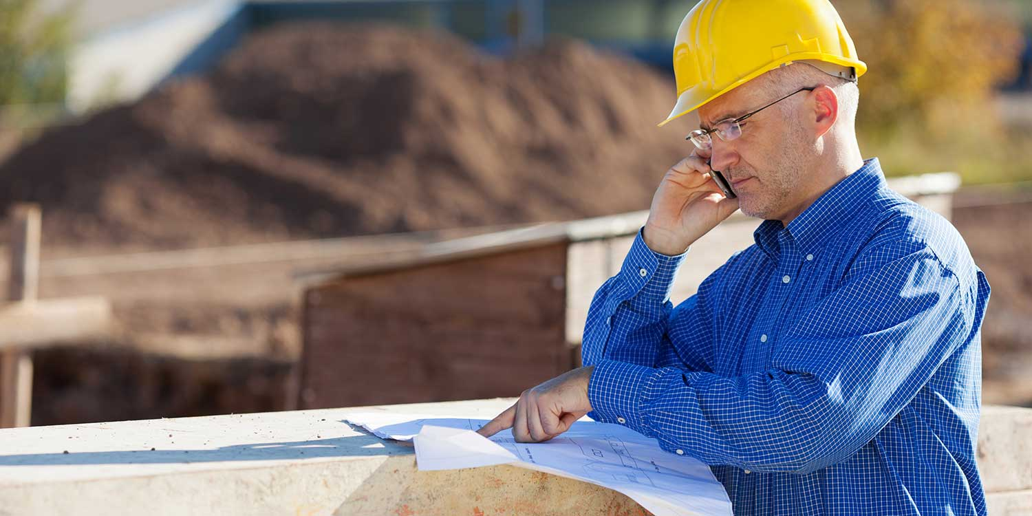 Pinal County worker looking at blueprints and talking on a cell phone
